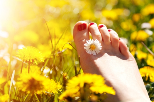 Foot of a young woman with a spring flower in fingers lying on s